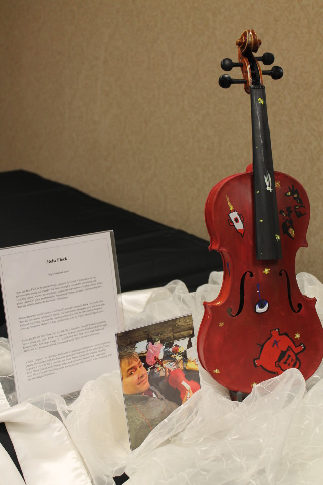 "Violin painted by musician Béla Fleck. The drawings on this particular violin are to convey several things: something about our city (the rocket), the fireflies are representative of our Crescen-Dough Auction theme, and he wanted to add something about himself. The name of his second album is ""Flight of the Cosmic Hippo."" The drawing at the bottom right is a red hippo, which is representative of his new album ""Flight of the Cosmic Hippo."" We have added a link to the YouTube video: https://www.youtube.com/watch?v=1iYgf6PWYK8"